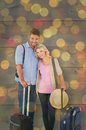 Composite image of attractive young couple ready to go on vacation against close up christmas lights Stock Image