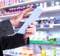 Composite image of businessman scrolling on his digital tablet against close up shelves drugs Stock Image