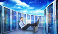 Composite image of businessman sitting on the floor with feet up on suitcase against server towers Stock Photos