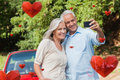 Composite image of cheerful mature couple taking pictures of themselves against valentines love hearts Royalty Free Stock Image