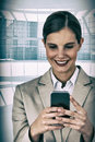 Composite image of close up of smiling businesswoman using mobile phone Royalty Free Stock Photo