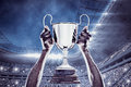 Composite image of cropped hand of athlete holding trophy against football stadium Royalty Free Stock Photography