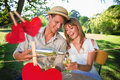 Composite image of cute couple drinking white wine together outside against hearts hanging on a line Stock Photo