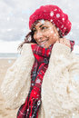 Composite image of cute smiling woman in warm clothing looking away at beach against snow falling Stock Photos