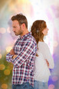 Composite image of depressed couple standing back to back Royalty Free Stock Photo