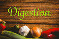 Composite image of digestion against various vegetables on wooden table Stock Image