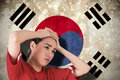 Composite image of disappointed football fan looking down against south korea flag Royalty Free Stock Photography