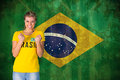 Composite image of excited football fan in brasil tshirt against brazil flag grunge effect Stock Images