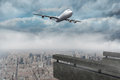 Composite image of flying airplane against gloomy city Royalty Free Stock Image