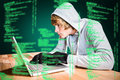 Composite image of focused man with hoodie typing on laptop Royalty Free Stock Photo