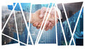 Composite image of handshake between two business people against city skyline Royalty Free Stock Photography