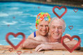 Composite image of happy mature couple in the swimming pool against hearts Royalty Free Stock Photo