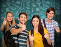 Composite image of happy students gesturing thumbs up at college corridor Royalty Free Stock Photo