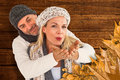 Composite image of husband hugging wife from behind as she blows kiss in air against overhead wooden planks Royalty Free Stock Photo