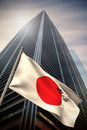 Composite image of japan national flag against low angle view skyscraper Stock Photo