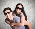 Composite image of man giving his pretty girlfriend a piggy back against weathered surface Stock Images