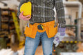 Composite image of manual worker wearing tool belt while holding gloves and helmet Royalty Free Stock Photo