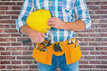 Composite image of manual worker wearing tool belt while holding hammer and helmet Royalty Free Stock Photo