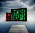 Composite image of matrix on tablet and smartphone screens against cloudy sky over ocean Royalty Free Stock Image
