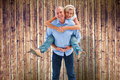 Composite image of mature man carrying his partner on his back men against wooden planks background Stock Photos