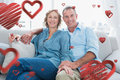 Composite image of middle aged couple relaxing on the couch against happy valentines day Royalty Free Stock Photos