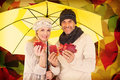 Composite image of portrait of couple holding autumn leaves while standing under yellow umbrella against autumnal leaf pattern in Stock Images