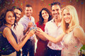 Composite image of portrait of friends drinking shots while standing together Royalty Free Stock Photo