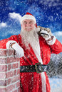 Composite image of portrait of santa claus carrying bag full of gifts Royalty Free Stock Photo