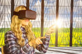 Composite image of pretty casual worker using oculus rift against nature scene Royalty Free Stock Photo