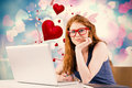 Composite image of pretty redhead working on laptop against valentines heart design Royalty Free Stock Images