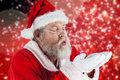 Composite image of santa claus in eyeglasses blowing invisible snow Royalty Free Stock Photo