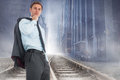 Composite image of serious businessman holding his jacket against cityscape projection over railway tracks Royalty Free Stock Photography