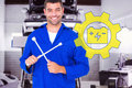 Composite image of smiling male mechanic holding lug wrench against auto repair shop Stock Photos
