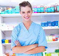 Composite image of smiling nurse in blue scrubs posing with arms crossed against close up shelves drugs Stock Photography
