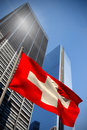Composite image of swiss national flag against low angle view skyscrapers Stock Photo