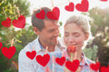 Composite image of young couple holding a flower in park against hearts hanging on line Stock Images