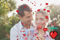 Composite image of young couple holding a flower in park against valentines day greeting Royalty Free Stock Photo