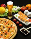 Composition of beer sushi and pizza on black background Royalty Free Stock Images