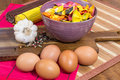 Composition of colorful pasta in a cup, garlic, pepper and eggs on a wooden board Royalty Free Stock Photo
