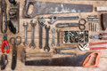 Composition of construction tools on an old battered wooden surface of tools: pliers, pipe wrench, screwdriver, hammer, metal shea Royalty Free Stock Photo