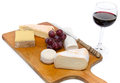 Composition of different cheeses on a wooden cutting board isolated white Stock Image