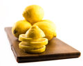 Composition of fresh and cut lemons on a wooden board and white background Royalty Free Stock Photo