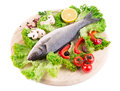 Composition of fresh seabass and vegetables on a white background Royalty Free Stock Photography