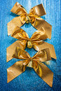 Composition of golden bows with bells on old painted blue color wooden board Stock Images