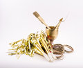 Composition of golden objects - glass, brush, spatula, party whistles