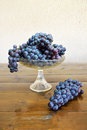 Composition with grapes fruit bowl and a bunch of on a wooden table Royalty Free Stock Photos