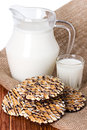 Composition milk in a jug glass and cookies on blue wooden background Royalty Free Stock Photos