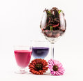 Composition of pink and violet colored cocktails, glass full of flowers and two flowers on a white background Royalty Free Stock Photo