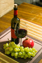 Composition of pomegranate, yellow muscat grape, glass and bottle of red wine on a wooden board Royalty Free Stock Photo
