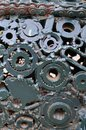 A composition of a set of gears and car parts that are welded to each other and painted green. Grunge steampunk textur
